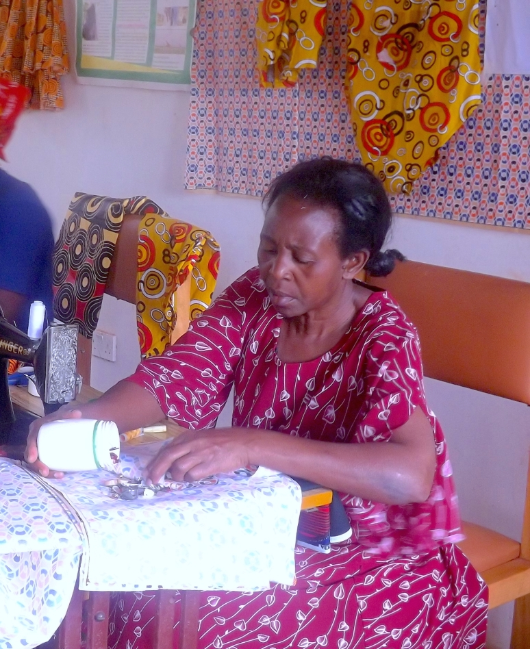 Mamma Joy - Main Teacher Mamma Joy is the heart and soul of the Dewe Project. It is thanks to her design, tailoring and teaching skills that the lily pad project is being a success. Main teacher for women, they all look up to her as a model, an inspiration and a leader.